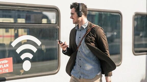 Ein junger Mann geht an einem Zug mit Werbung für freies WLAN vorbei.