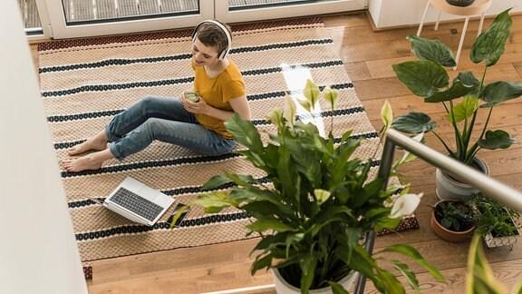 Zimmerpflanzen in eienm Raum, eine Frau hört Musik