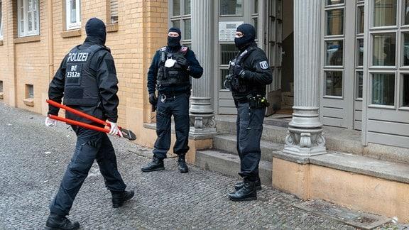 Ein Polizist geht bei einer Razzia mit einem Bolzenschneider in ein Haus