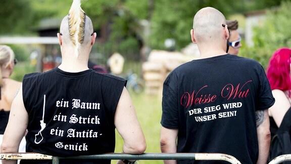 """Auf den T-Shirts von zwei Teilnehmern des Festivals Tage der nationalen Bewegung€œ in Themar steht ein Baum ein Strick ein Antifa-Genick und Weisse Wut der Sieg wird unser sein!"""" geschrieben."""