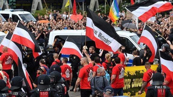 """Teilnehmer einer Demonstration der rechtsextremen NPD-Nachwuchsorganisation Junge Nationaldemokraten ziehen unter dem Motto """"Tag der deutschen Zukunft"""" durch die Stadt an einer Gegenkundgebung (hinten) vorüber."""