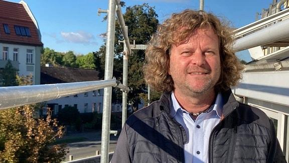 Raumausstatter Andreas Dieckmann aus Elbingerode steht auf einem Baugerüst.