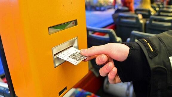 In der Straߟenbahn entwertet ein Fahrgast seinen Fahrschein
