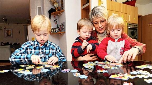Familienpatin Ruth Friedrich spielt mit Luca Pascal (5 Jahre, re.) und den dreijährigen Zwillingen Marc-Leon (li), Julien-Marcel (Mitte).