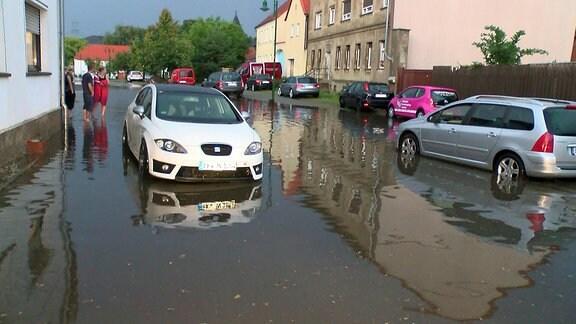 Autos und Menschen auf überschwemmter Straße
