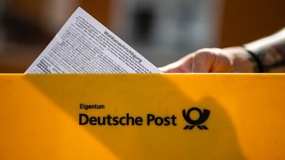 Ein Briefträger der Deutschen Post hält eine Wahlbenachrichtigung in einer Hand.
