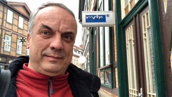 Mann mit grauen haaren und roten Fleece-Pullover macht ein Selfie vor einem Fachwerkhaus mit MDR-Logo