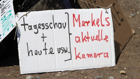 Plakat mit Aufschrift Tagesschau und Heute gleich Merkel s aktuelle Kamera