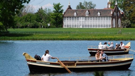 Besucher des Garteinreiches fahren im Wörlitzer Park auf Gondeln.