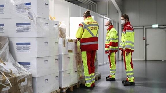 Mitarbeiter bei den Materialkisten vor dem Auspacken im neuen Impfzentrum in Magdeburg