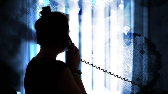 Eine Frau steht vor einem Fenster und telefoniert.