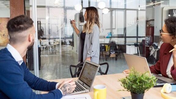 Geschäftsfrau erklärt männlichen und weiblichen Unternehmern im Büro die Geschäftsstrategie an einer Glasscheibe.