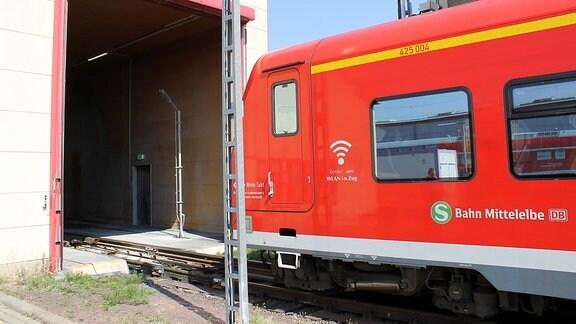 eine rote S-Bahn steht vor einem rot eingerahmten Tor