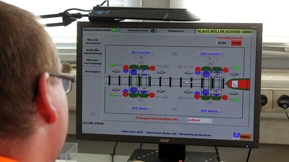 ein Mann schaut auf einen Bildschirm mit einer schematischen Darstellung einer Zugwaschanlage