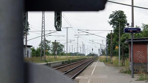 Entlang eines gepflasterten Bahnsteigs führt eine zweigleisige elektrifizierte Bahnstrecke.