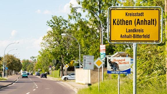 Neben einer Straße steht ein Ortseingangsschild der Stadt Köthen im Landkreis Anhalt-Bitterfeld.