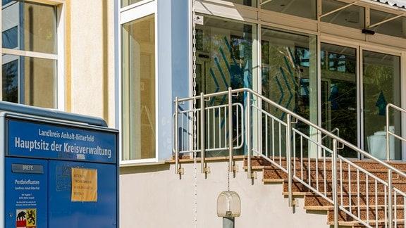 Neben dem Eingang zu einem Gebäude weist ein Schild auf die Verwaltung des Landkreises Anhalt-Bitterfeld in Köthen hin.