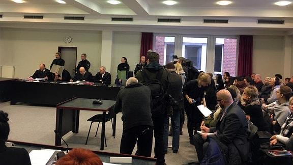Im Gerichtssaal haben sich viele Reporter versammelt. Sie halten mit ihren Kameras auf den Angeklagten und seine Verteidiger.