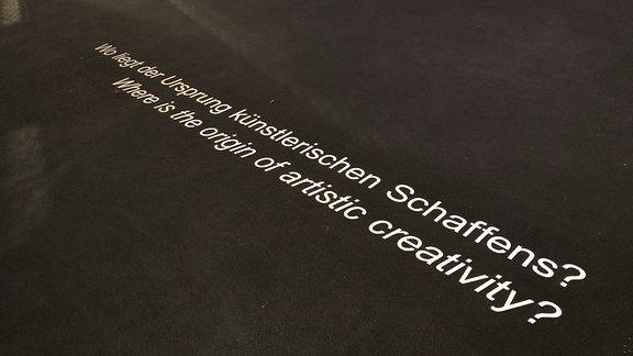 Auf schwarzem Hintergrund steht mit weißer Schrift geschrieben: -Wo liegt der Ursprung des künstlerischen Schaffens?-