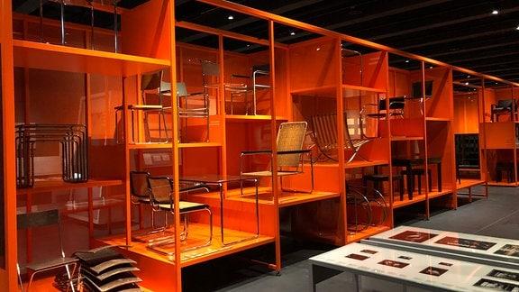 Vor orangenem Hintergrund stehen mehrere Stühle im Bauhaus Museum in Dessau