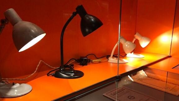 Lampen stehen auf einer orangefarbenen Platte im Bauhaus Museum in Dessau