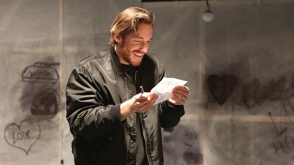 Schauspieler Andreas Hammer hält einen Zettel in der Hand und blickt lächelnd darauf.