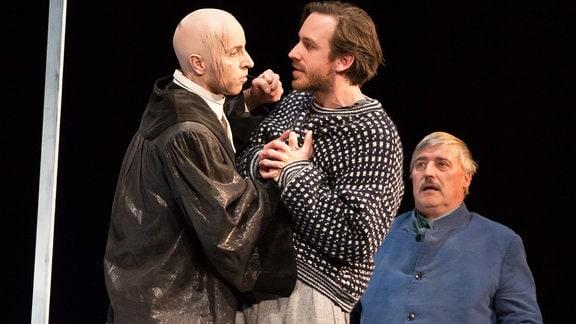 Szene am Theater mit drei Männern, von denen sich zwei eine Auseinandersetzung liefern. Ein dritter Mann sitzt auf einer Bank und sieht angespannt zu.