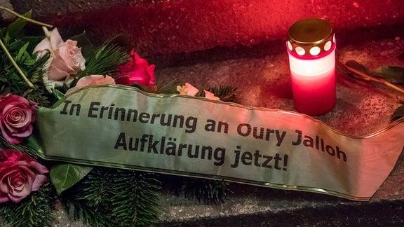 In Erinnewrung an Oury Jalloh Aufklärung jetzt steht auf einem Band, daneben Blumen und eine Kerze