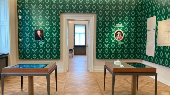 Galerie mit Bilder an grünen Wänden und Ausstellungstischen.