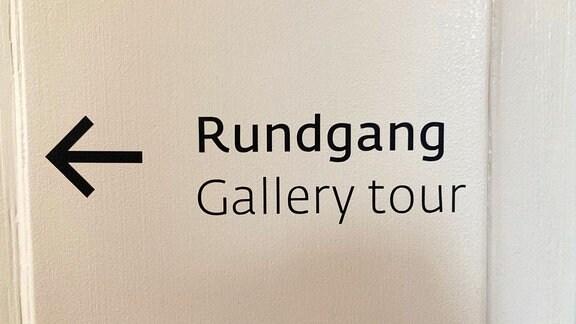 """Schild """"Rundgang Gallery Tour"""" und Pfeil."""