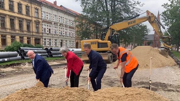 Vier Personen stechen mit einem Spaten in einen großen Sandhaufen.