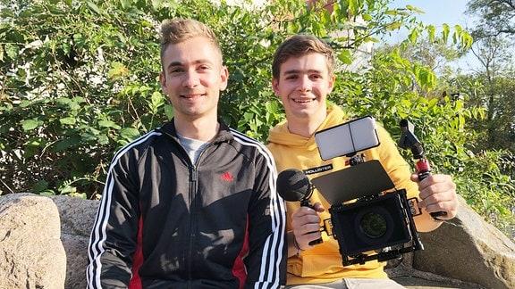 Zwei junge Männer sitzen auf einer Bank und lächeln in die Kamera, in der Hand halten sie eine Kameraausrüstung.