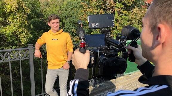 Ein junger Mann im gelben Pulli steht an ein Brückengeländer gelehnt und spricht in eine Kamera. Die wird von einem zweiten jungen Mann bedient, ihn sieht man nur von hinten.