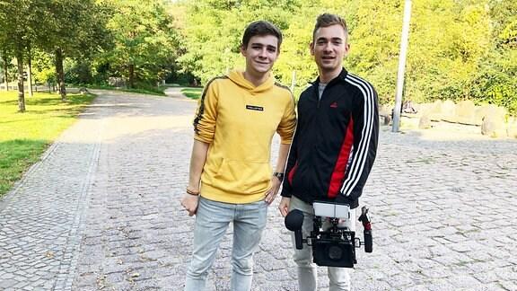 Zwei junge Männer stehen lässig auf einem Weg in einem Park. In der Hand hält einer der beiden eine Kameraausrüstung.