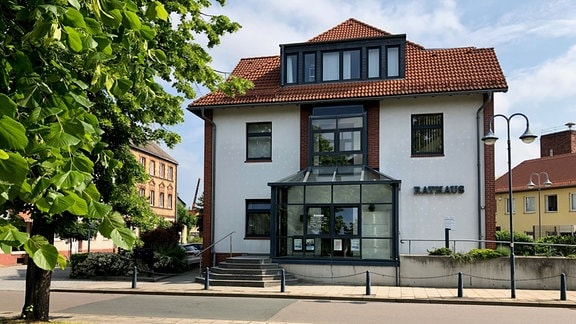 Ein weißes Haus mit Glasvorbau. An der Fassade steht Rathaus. Eine Treppe führt zum Eingang