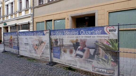 Bauzaun vor einem Gebäude in Wittenberg, in dem Wohnungen entstehen sollen.