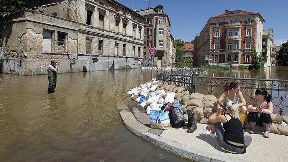 Jugendliche sitzen 2013, neben Sandsäcken am Hochwasser im Ortsteil Klaustorvorstadt in Halle an der Saale