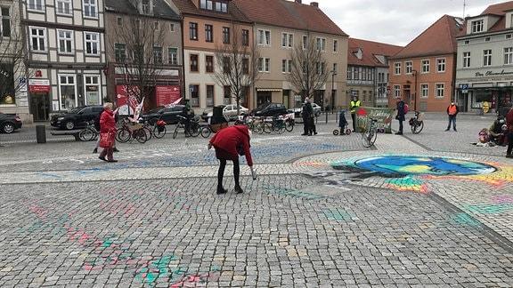 Menschen auf einem Marktplatz stehen mit Plakaten um etwas, was auf dem Bodengesprayed wird.