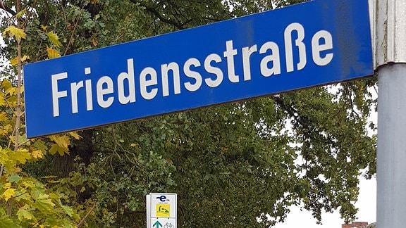 Straßenschild Friedensstraße an Straße mit Bäumen in Aulosen