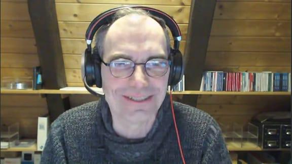 Ein Mann mit Brille, der uns bei einer Videokonferenz anschaut
