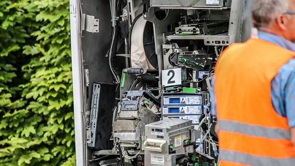Polizist untersucht einen gesprengten Fahrkartenautomaten der Bahn.