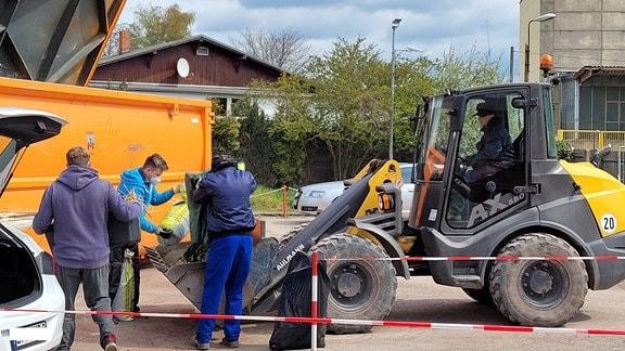 Drei Männer entladen einen Kofferraum. Dahinter stehen ein orangefarbener Container und ein Radlader.