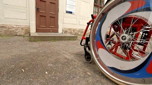 Detailaufnahme eines Rollstuhls, es ist von schräg unten eines der Räder zu sehen