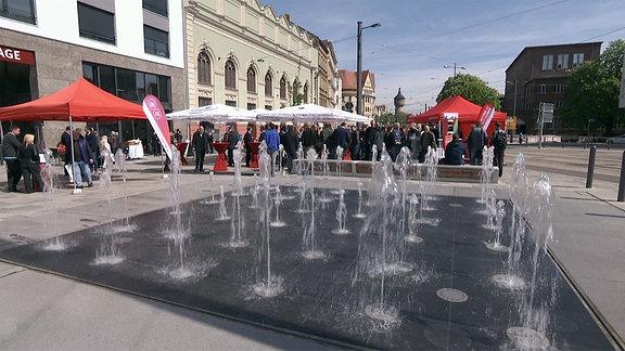 Ein Springbrunnen sprudelt am umgestalteten Steintorplatz in Halle