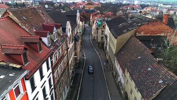 Blick von oben auf eine Straße mit vielen verfallenden Häusern an den Staßenrändern