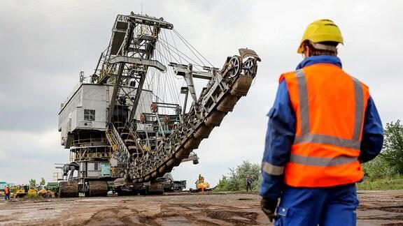 Ein Mitarbeiter der Mitteldeutschen Braunkohlengesellschaft mbH (MIBRAG) überwacht den Umzug des Eimerkettenbaggers 351
