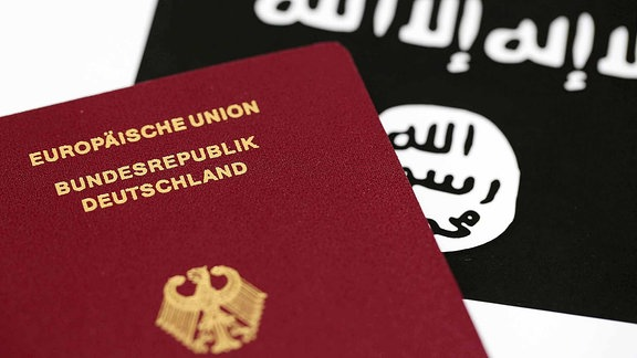 Ein Reisepass der Bundesrepublik Deutschland vor der Flagge des Islamischen Staates.