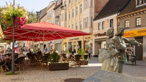 Vor einem Café sind an einem steinernen Brunnen Skulpturen in Weißenfels zu sehen.