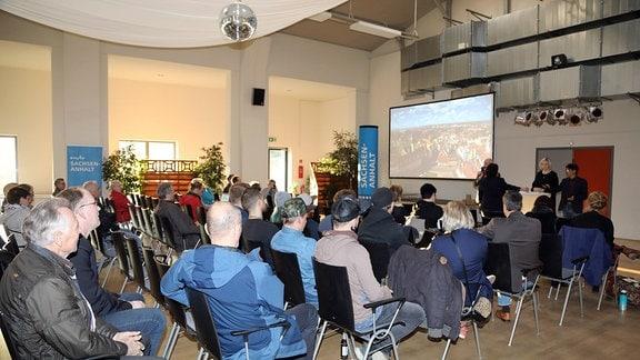 Zuschauer schauen einen Film auf einer Leinwand.
