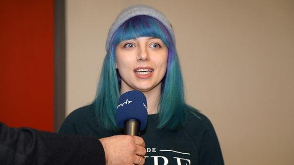 Eine junge Frau mit türkis-lila gefärbten Haaren und Mütze im Interview.
